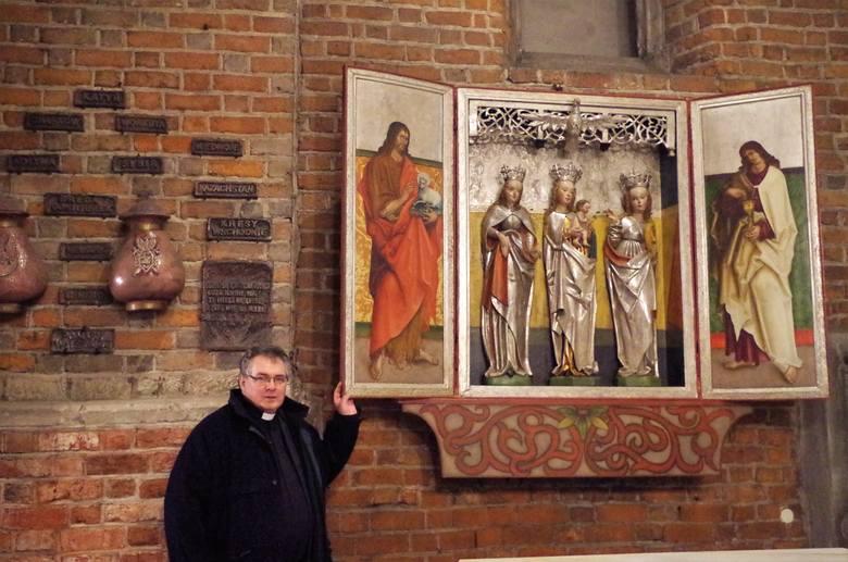 Proboszcz katedry, ks. Waldemar Klinger przy otwartym gotyckim ołtarzu.