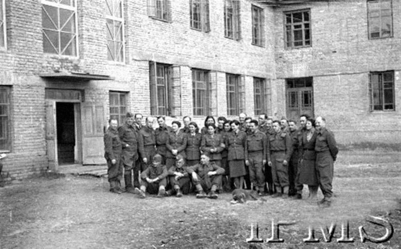 Ryc. 6. Marzec 1942 r., Jangi-Jul, Uzbekistan, ZSRR. Grupa pracowników oddziału propagandy przed gmachem Sztabu Armii Polskiej, od strony placu ćwiczebnego.