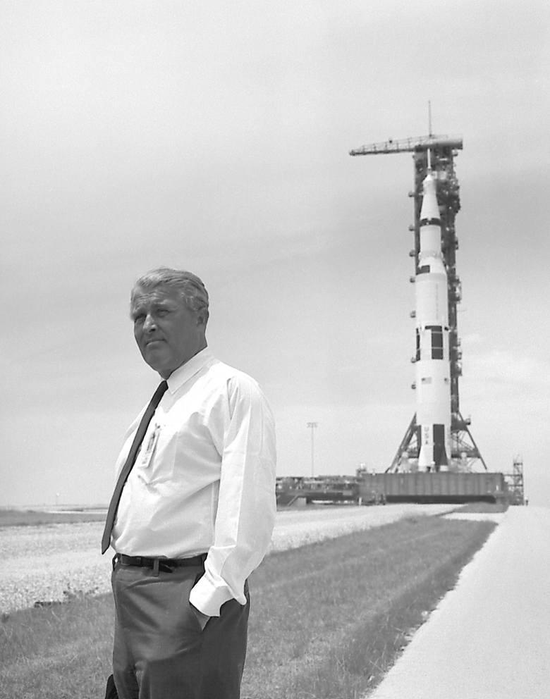 Wernher von Braun pozujący na tle rakiety Saturn V.