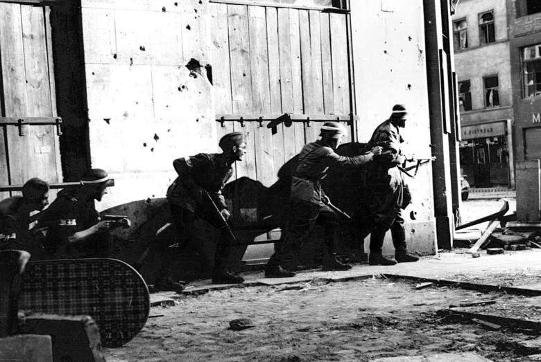 """Powstańcy z kompanii """"Koszta"""" przebiegający obok narożnika kamienicy wydawnictwa Gebethner i Wolff przy ul. Sienkiewicza 9. Sierpień 1944 r."""