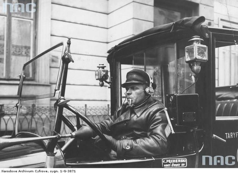 """Mężczyzna palący fajkę za kierownicą warszawskiej taksówki ze zwijanym brezentowym dachem nad miejscem kierowcy i z kabiną pasażerską wyposażoną w radioodbiornik ze słuchawkami. Widoczny klakson oraz boczne lampy elektryczne oświetlające taksówkę.  <font color=""""blue""""><a..."""