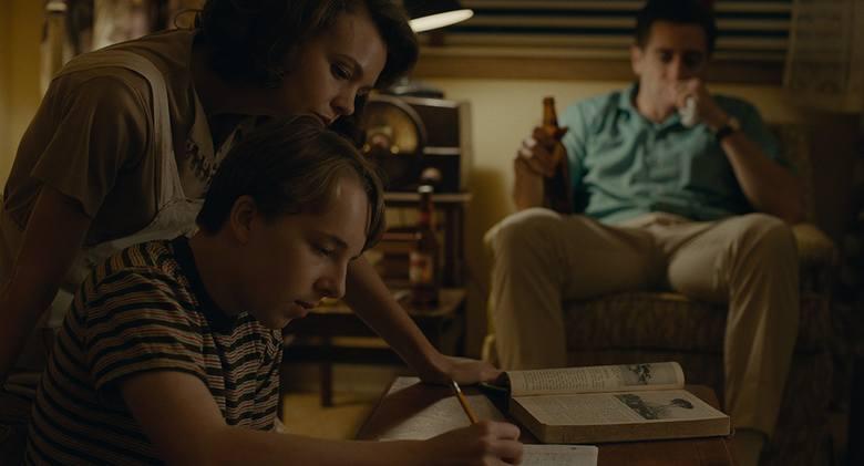 Carey Mulligan, Jake Gyllenhaal (w tle) i Ed Oxenbould nad pracą domową. Pozornie szczęśliwa rodzina na chwilę przed kryzysem. Kadr z filmu Wildlife,