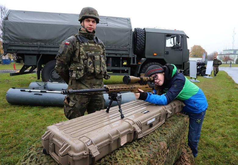 """Najmłodsi uczestnicy niedzielnego pikniku wojskowego na Sadkowie mogli """"przymierzyć się"""" do pistoletu."""