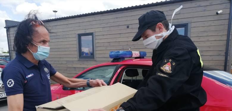 Przemysław Walewski przekazuje maseczki i fartuchy ochronne Pawłowi Milczarkowi