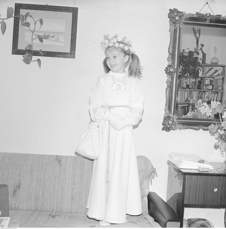 <strong>1980 rok</strong><br /> <br /> W latach 80. sukienki komunijne - tak jak i cała moda damska - podążały w stronę falban, bufiastych rękawów i poduszek na ramionach (o ile rodzice nie zdecydowali się na prostą albę - tak jak na fotografii).