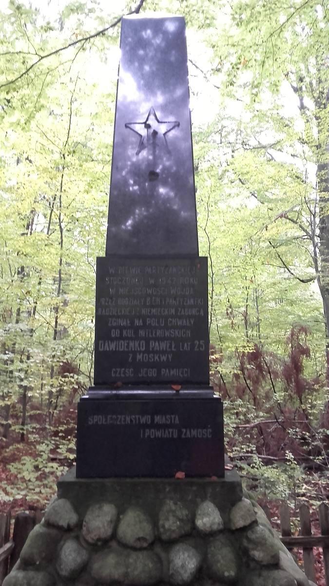 W lesie jest też obelisk upamiętniający jednego z uczestników tych walk z Niemcami, w czasie bitwy pod Wojdą. Paweł Dawidenko z Moskwy w chwili śmierci miał 25 lat. - Cekaemista Paweł Dawidenko brawurowo walczył  na skraju lasu, od strony Kosobud. Zginął - dodaje zamojski przewodnik PTTK, Edward...