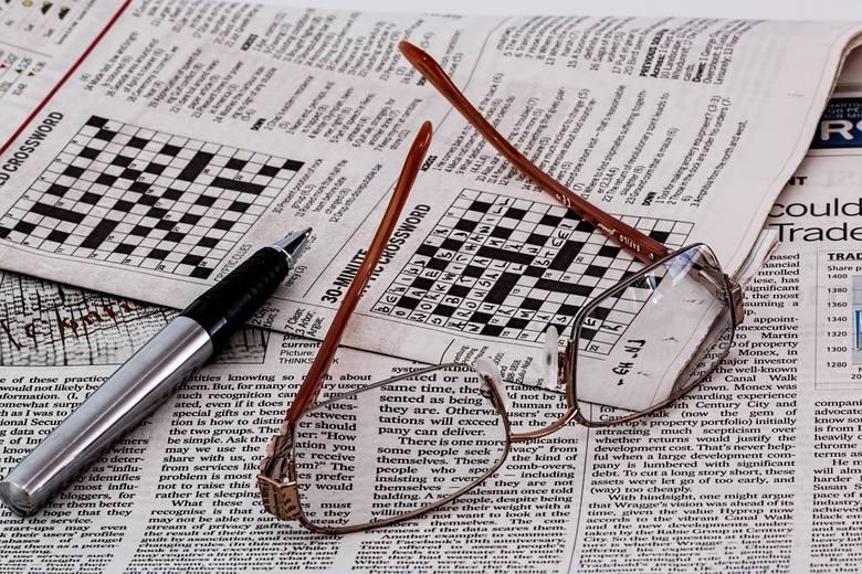 Gazeta z krzyżówkami, na niej okulary
