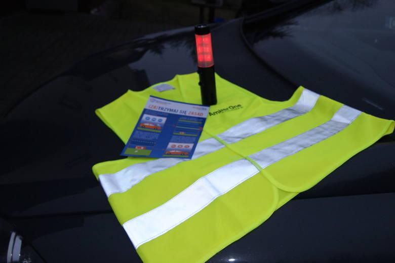 """Kierowcy przy grudziądzkim węźle autostradowym otrzymują od policjantów kamizelki odblaskowe, ulotki informacyjne o zasadach zatrzymywania się na autostradzie podczas awarii pojazdu bądź wypadku oraz tzw. """"latarki życia""""."""