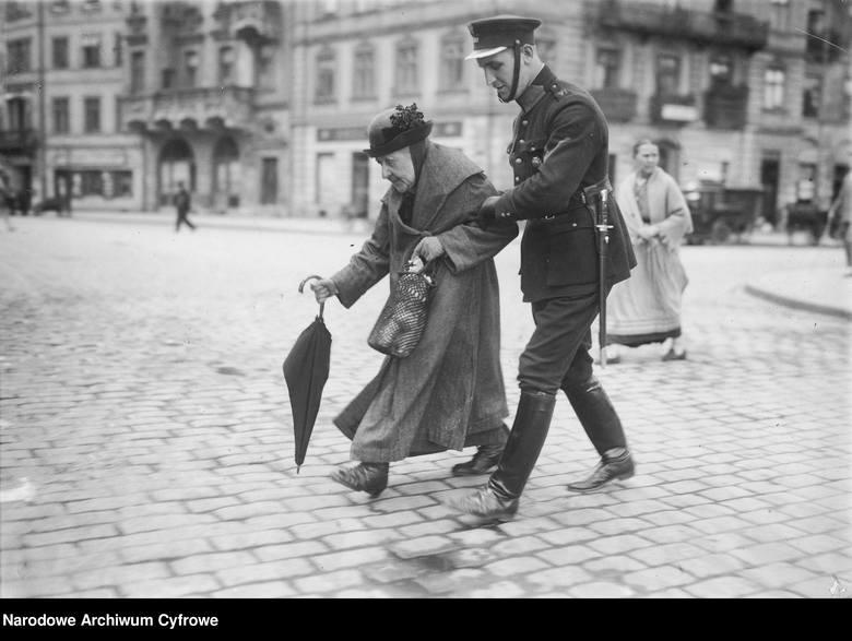 Policjant przeprowadzający staruszkę przez ulicęNa zdjęciu: policjant przeprowadzający staruszkę na drugą stronę Krakowskiego Przedmieścia w Warszawie.