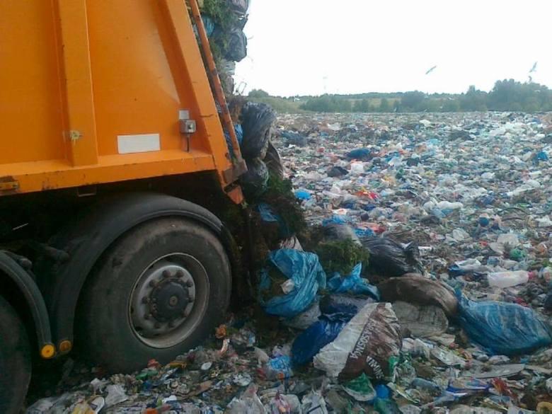 Worki z odpadami zielonymi wyrzucane na składowisko