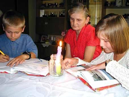 Łukasz i Joasia psują oczy odrabiając lekcje przy świeczkach.