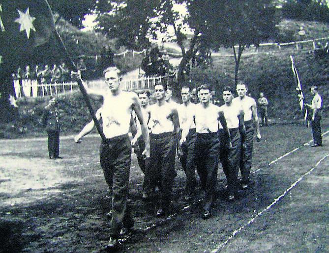 Uroczysta parada australijskich jeńców pod narodową flagą przed sportowymi zawodami w niemieckim obozie w Toruniu.