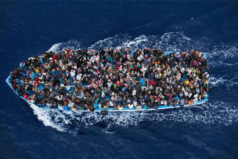 """WORLD PRESS PHOTO 2015. Drugie miejsce w kategorii """"Wiadomości ogólne - zdjęcie pojedyncze"""". Uchodźcy na przepełnionej ponad wszelką miarę, nabierającej wody łodzi - ok 20 na północ od Libii."""