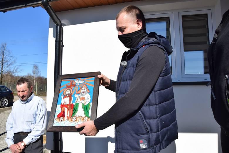 Piotr Tylek prezentuje I nagrodę w olszowickim konkursie - obraz malowany na szkle Trójca Przenajświętsza autorstwa artysty ludowego Zdzisława Słoniny