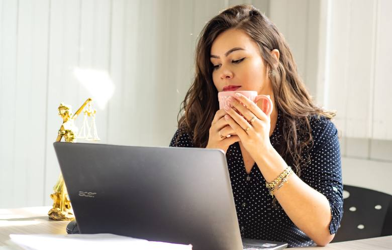 Na zdjęciu: dziewczyna z kubkiem siedząca przy biurku i patrząca na ekran laptopa