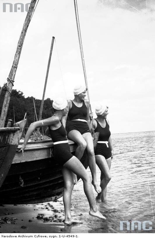 Kobiety w kostiumach kąpielowych przy łodzi