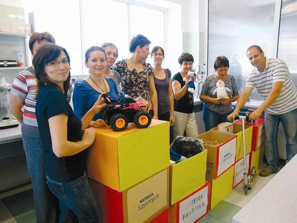 Pracownicy Nutricia chętnie angażują się w akcje na rzecz lokalnej społeczności. Na zdjęciu pokazują nagrody z loterii, z której dochód pomógł sfinansować