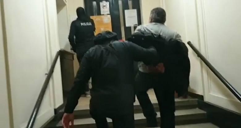 Jeden z zatrzymanych doprowadzany na komendę policji
