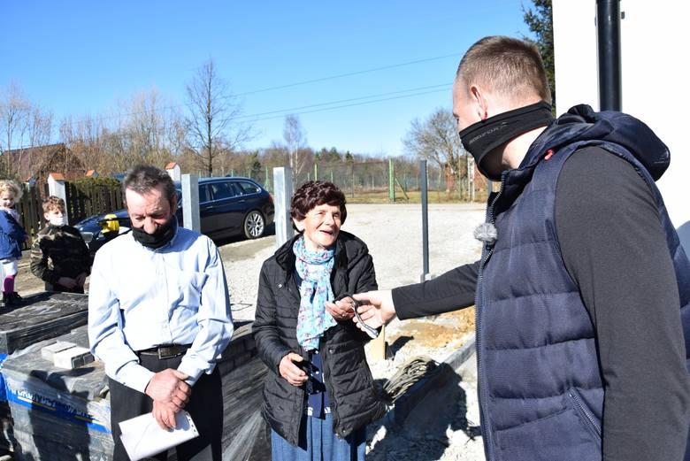 Przekazanie kluczy do nowego domu w Olszowicach. Gospodarzom Teresie Młynarczyk i jej synowi Zbigniewowi wręczył je sąsiad i strażak Piotr Tylek