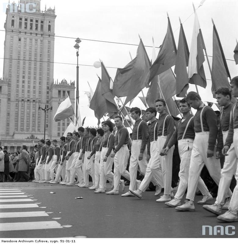 Uczestnicy pochodu z flagami przy Pałacu Kultury i Nauki.