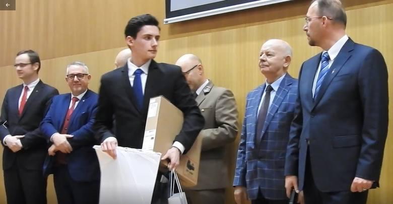 Piotr Pisarek odbiera od kapituły nagrody za wygranie konkursu wiedzy o Romanie Dmowskim