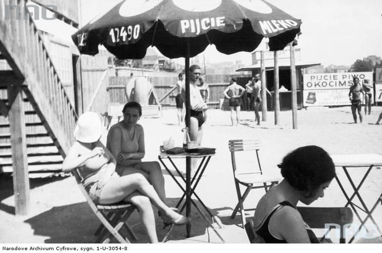 """Plażowicze podczas wypoczynku pod parasolem z napisem """"Pijcie mleko"""". W tle reklma z napisem """"Pijcie piwo Okocimskie""""."""