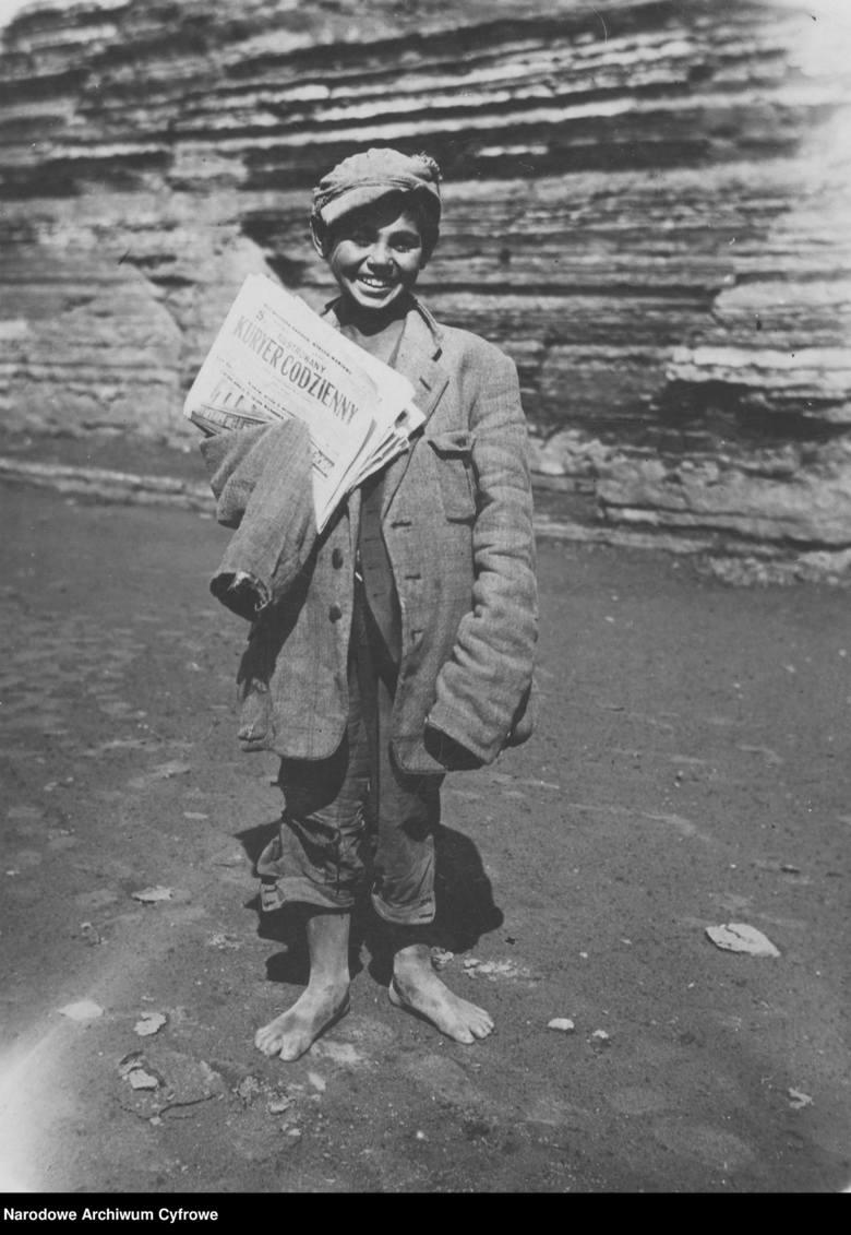 """Na zdjęciu: Zeylyk Rozemblat, uliczny sprzedawca gazet, trzyma egzemplarze """"Ilustrowanego Kuriera Codziennego"""". Fotografia sytuacyjna."""