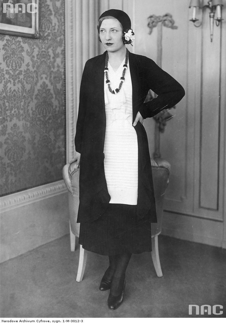 Modelka w czarnym berecie przybranym białym kwiatem prezentuje komplet Georgette. Nowością jest plisowana spódnica i plisa na dole żakietu.