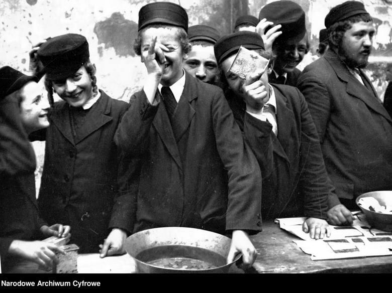 Lata trzydzieste, tuż przed wojną, miasto nieznane.  Chłopcy prawdopodobnie w czasie żydowskiego święta są zajęci beztroską grą przy straganie. Zachęcają