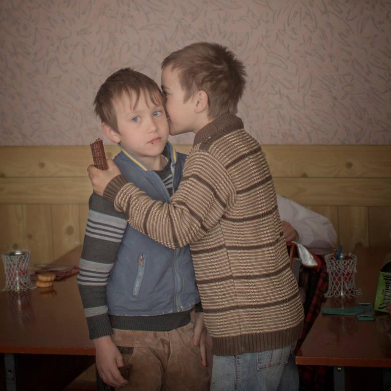 """WORLD PRESS PHOTO 2015. Drugie miejsce w kategorii """"Życie codzienne - zdjęcie pojedyncze"""". Bracia - Igor i Artur dzielą się czekoladą podczas 9. urodzin. Są sierotami z Mołdawii."""