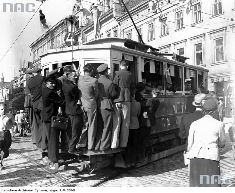 """Tramwaj linii """"4"""" w Krakowie obwieszony pasażerami jadącymi na zderzaku.  <font color=""""blue""""><a href=""""http://www.audiovis.nac.gov.pl/obraz/85979/78a7c0d86da09098e45b969cb38306d4/""""><b>Zobacz zdjęcie w zbiorach NAC</b></a> </font>"""