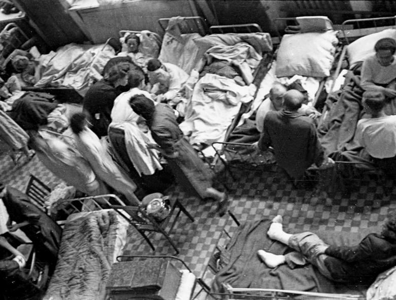 Ranni leżący na korytarzu powstańczego szpitala, prawdopodobnie w budynku PKO, sierpień 1944 r.
