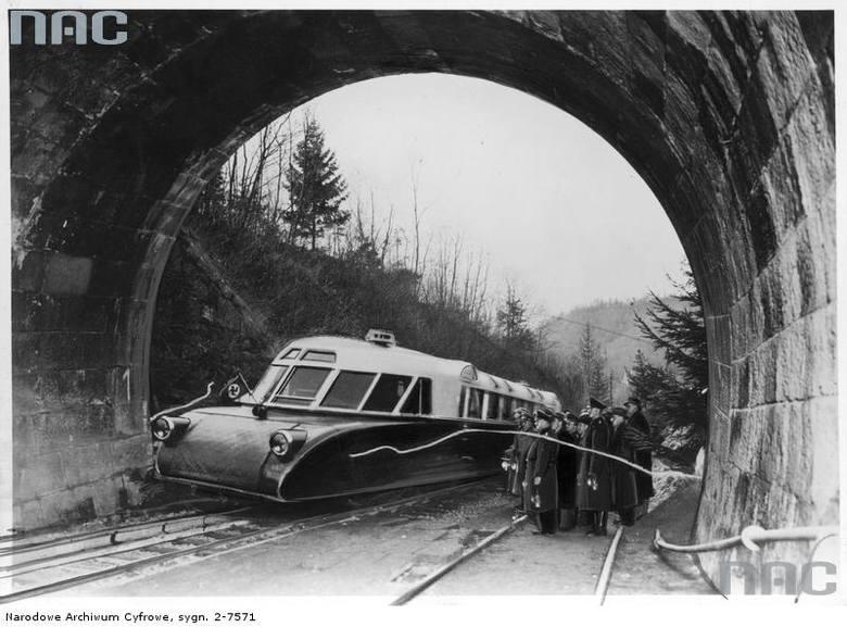 """Otwarcie odbudowanego tunelu kolejowego. Przejazd wagonu spalinowego &#8222;lux-torpeda&#8221; przed grupą urzędników i oficerów. <font color=""""blue""""><a href="""" http://www.audiovis.nac.gov.pl/obraz/11954/ef4bdda92673cf385f4ebe32cdc1cb18/""""><b>Zobacz zdjęcie w zbiorach NAC</b></a> </font>"""