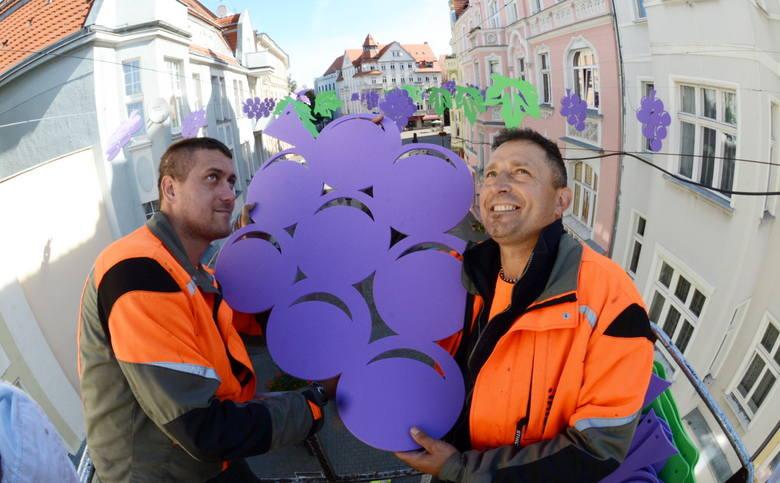 Michał Potyraj i Marek Urbaniak zawieszają ozdoby winobraniowe na deptaku