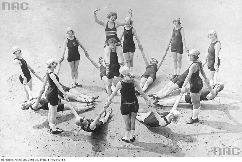 Grupa osób w kostiumach kąpielowych podczas zabawy na plaży