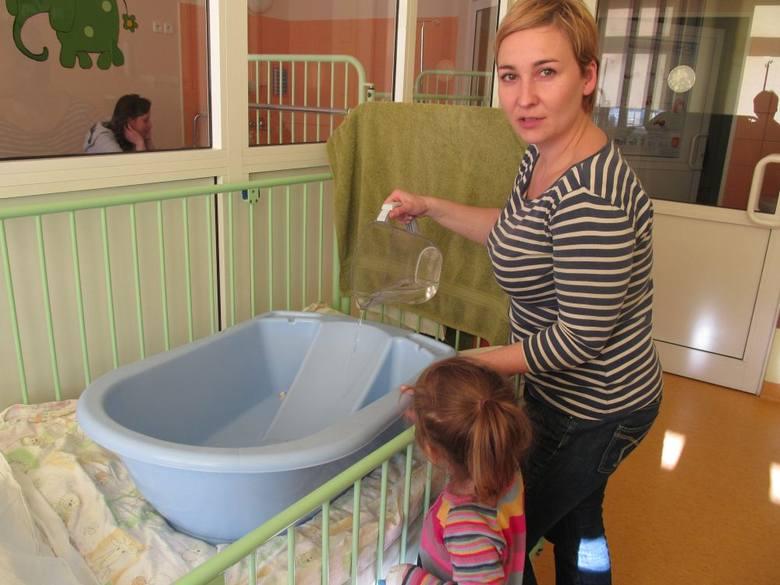 Monika Kocięba-Żabska wodę grzeje w czajniku, następnie wlewa ją do wanienki. Zmuszona jest kąpać trzyletnią Lidkę w ten sposób, ponieważ ze szpitalnego