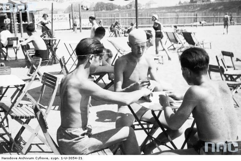 Plażowicze podczas gry w karty przy stoliku na plaży Towarzystwa Uniwersytetu Robotniczego.
