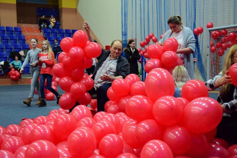 """W hali sportowej odbyła się akcja """"Janikowo Murem za Owsiakiem"""". Mieszkańcy nadmuchali setki czerwonych balonów. Utworzyli z nich wielkie"""
