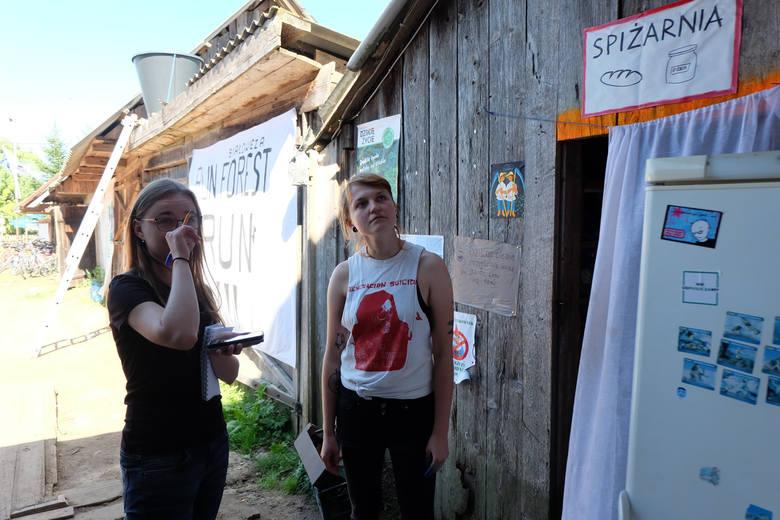 """Monika (z prawej) oprowadza nas po obozie. Pokazuje zawieszony na ścianie stodoły regulamin, spiżarnię oraz """"łazienkę"""" z ogromnym wiadrem przymocowanym do dachu."""