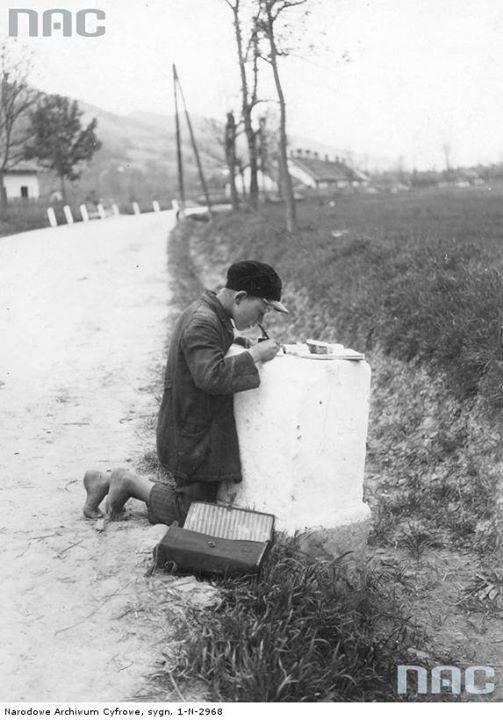 Uczeń Józef Drożdż odrabia lekcje na kamieniu kilometrowym.