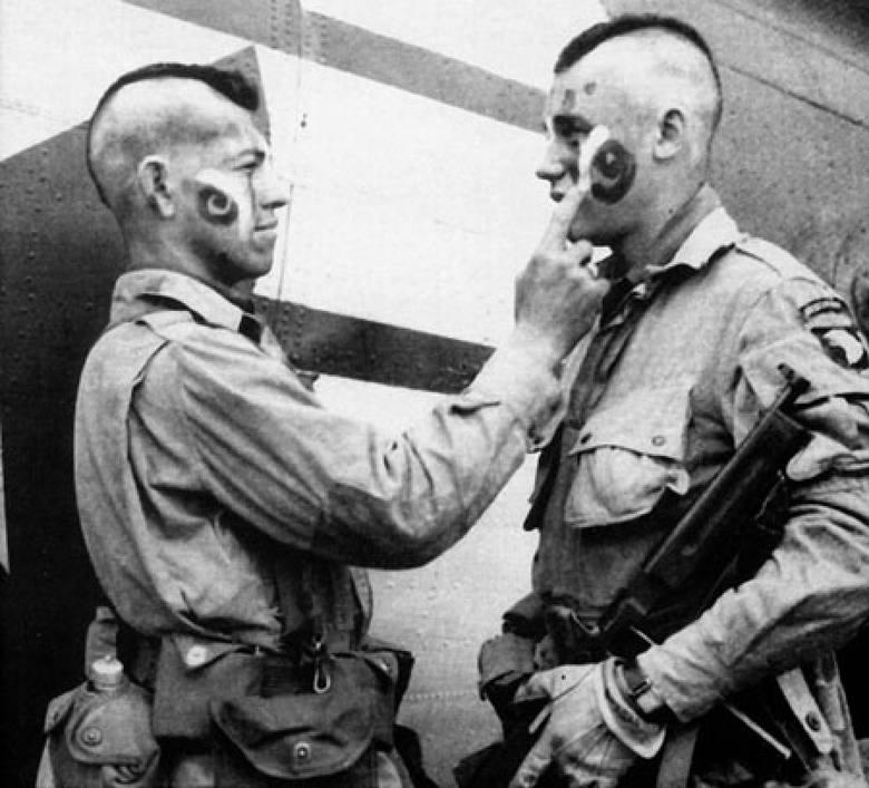 """Żołnierze """"Brudnej Trzynastki"""" malują sobie twarze przed wejściem do samolotu (5 czerwca 1944 r.)"""