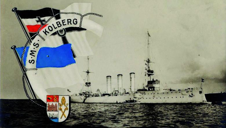 """Lekki krążownik SMS """"Kolberg"""" uwieczniony na pocztówce z epoki. Z lewej strony widoczna badnera cesarskiej marynarki wojennej oraz flaga i herb mias"""