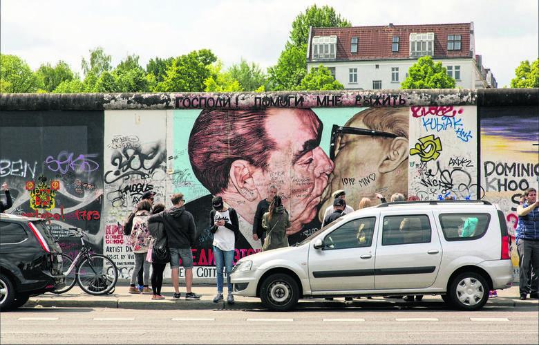 """Mur Berliński stał się niezwykłą galerią sztuki. Najbardziej znanym obrazem jest """"Brotherly Kiss"""", którego autorem jest Rosjanin  Dimitri Vrubel, pokazujący"""