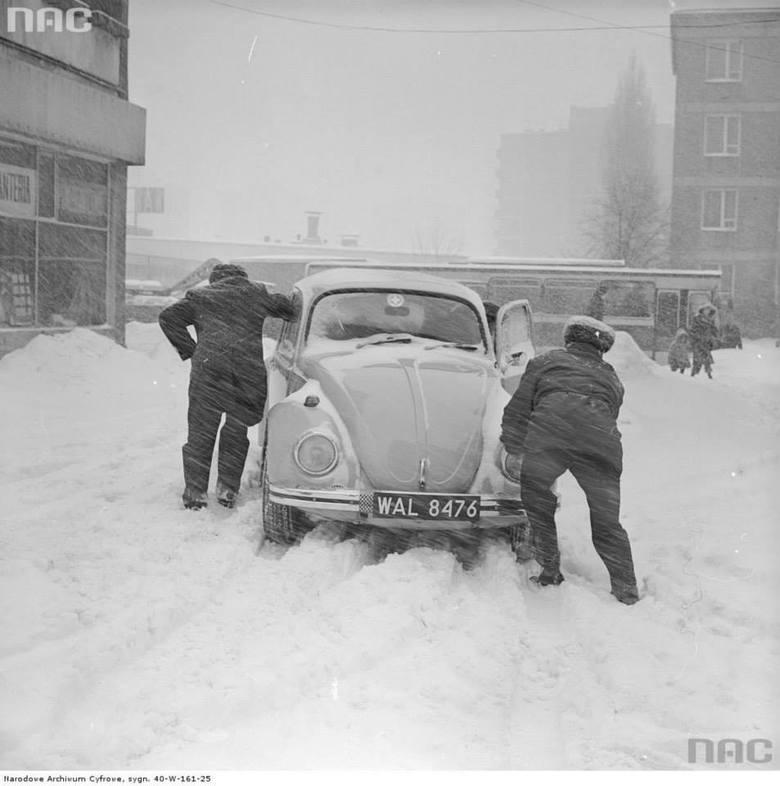 Mężczyźni pchający samochód Volkswagen Garbus. Z lewej budynek przy ul. Malczewskiego