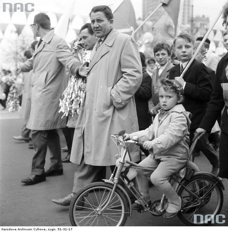 Uczestnicy pochodu na ul. Marszałkowskiej. Widoczne dziecko jadące na rowerze.