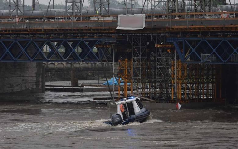 Kraków. Funkcjonariusze policji wodnej chronią most kolejowy przed napływającymi konarami