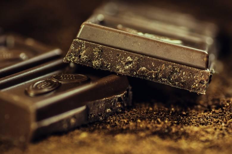 Dwie kostki ciemnej, gorzkiej czekolady przedstawione w dużym zbliżeniu.