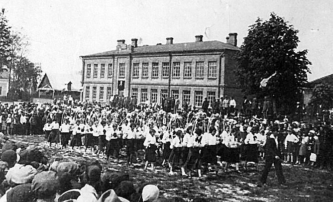 Parada młodzieży z okazji święta Trzeciego Maja na rynku <br /> w  Międzyrzecu Koreckim przed szkołą, do której uczęszczał Zbigniew Okoń – późniejszy dokumentalista ludobójstwa na Wołyniu – i w której uczyła jego wychowawczyni Tania Silberstein, zamordowana przez Niemców, rok 1937.<br />