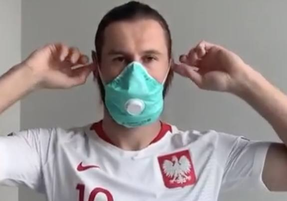 Grzegorz Krychowiak, piłkarski reprezentant Polski. w ochronnej maseczce.
