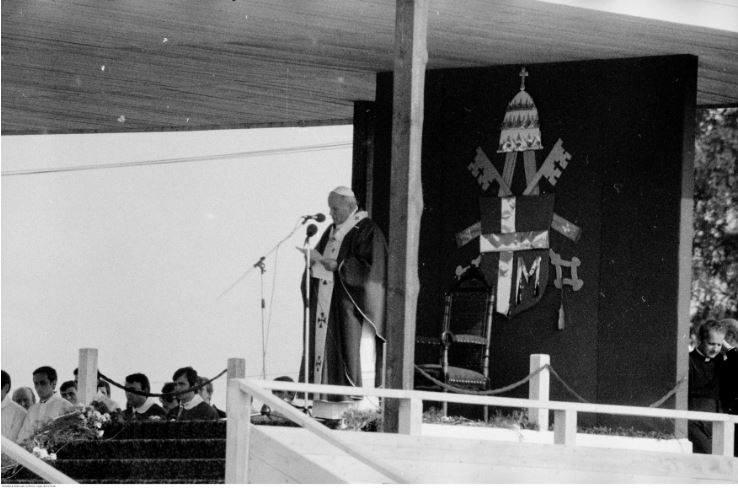 Pobyt papieża Jana Pawła II w Oświęcimiu-Brzezince podczas I pielgrzymki do Polski. Papież Jan Paweł II przemawia podczas mszy św. odprawianej na terenie byłego obozu koncentracyjnego Auschwitz II - Birkenau. W dekoracji ołtarza widoczny herb Jana Pawła II.<br /> Data wydarzenia: 1979-06-07